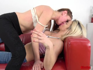 Blonde and brunette lesbians kissing and making out on sofa
